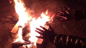 Θερμαίνει τα χέρια της τη νύχτα γύρω από την πυρά προσκόπων απόθεμα βίντεο