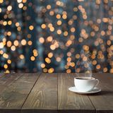 Θερμαίνοντας φλυτζάνι του καυτού μαύρου καφέ στον ξύλινο πίνακα στον καφέ Θολωμένη χρυσή γιρλάντα ως υπόβαθρο στενός κόκκινος χρό Στοκ Φωτογραφίες