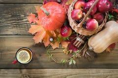 Θερμαίνοντας φλυτζάνι του τσαγιού, ντεκόρ της συγκομιδής φθινοπώρου, κολοκύθα, μήλα στον ξύλινο πίνακα πτώση 1 ζωή ακόμα Τοπ όψη Στοκ Εικόνες