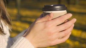 Θερμαίνοντας χέρια κοριτσιών και καφές κατανάλωσης μόνος, απολαμβάνοντας το ηλιόλουστο φθινόπωρο, έμπνευση φιλμ μικρού μήκους