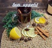 Θερμαμένο κρασί με ένα λεμόνι, την κανέλα, ένα anisetree, και μια επιγραφή bon appetit Στοκ εικόνα με δικαίωμα ελεύθερης χρήσης