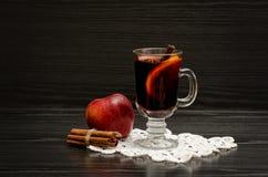 Θερμαμένο κρασί με τα καρυκεύματα σε μια πετσέτα δαντελλών, ένα μήλο και τα ραβδιά κανέλας μαύρο δάσος ανασκόπησης Στοκ φωτογραφίες με δικαίωμα ελεύθερης χρήσης