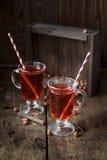 Θερμαμένο κρασί με τα ραβδιά κανέλας στο σκοτεινό ξύλινο υπόβαθρο Στοκ εικόνες με δικαίωμα ελεύθερης χρήσης
