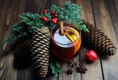 Θερμαμένο κρασί με τους κώνους, ένα λεμόνι, έναν ιουνίπερο, την κανέλα, ένα anisetree και ένα μήλο Στοκ Εικόνα
