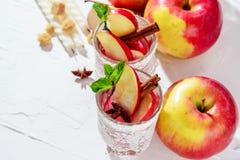 θερμαμένο κρασί στα γυαλιά διχτυών ψαρέματος σε ένα ελαφρύ υπόβαθρο, Apple, κανέλα, κρασί Στοκ φωτογραφία με δικαίωμα ελεύθερης χρήσης
