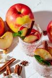 θερμαμένο κρασί στα γυαλιά διχτυών ψαρέματος σε ένα ελαφρύ υπόβαθρο, Apple, κανέλα, κρασί Στοκ Φωτογραφίες