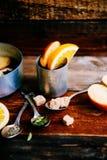 Θερμαμένο κρασί στην αγροτική κούπα με τα καρυκεύματα και τα συστατικά στο ξύλινο υπόβαθρο Η τοπ άποψη, επίπεδη βάζει Αναδρομική  Στοκ Εικόνα