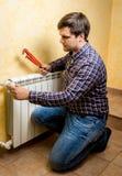 Θερμαντικό σώμα θέρμανσης καθορισμού Handyman με τις κόκκινες πένσες υδραυλικών Στοκ Φωτογραφία