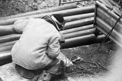 Θερμική μόνωση μονώνοντας σωλήνες συστημάτων θέρμανσης εργαζομένων με το φύλλο αλουμινίου στοκ φωτογραφία με δικαίωμα ελεύθερης χρήσης