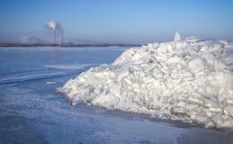 Θερμικός σταθμός και ένας σωρός του πάγου σε έναν παγωμένο ποταμό στοκ φωτογραφία