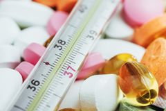 Θερμόμετρο και διαφορετικοί χρωματισμένοι τύποι χαπιών Ιατρική υγεία ή έννοια φαρμάκων Στοκ Φωτογραφίες