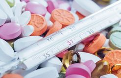 Θερμόμετρο και διαφορετικοί χρωματισμένοι τύποι χαπιών Ιατρική υγεία ή έννοια φαρμάκων Στοκ φωτογραφία με δικαίωμα ελεύθερης χρήσης