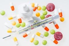 Θερμόμετρο, χάπια, ρινικός ψεκασμός στο λευκό Έννοια κρύου και γρίπης Στοκ εικόνα με δικαίωμα ελεύθερης χρήσης