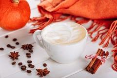Θερμός πλέξτε το μαντίλι και το φλυτζάνι του καυτού καφέ με τον αφρό Πορτοκαλιά κολοκύθα αποκριών, καρυκεύματα και άλλο ντεκόρ δι στοκ εικόνες με δικαίωμα ελεύθερης χρήσης