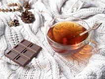 Θερμός πλέξτε το πουλόβερ, ένα φλυτζάνι του καυτού τσαγιού με τη σοκολάτα και τις χειμερινές διακοσμήσεις Στοκ Εικόνες