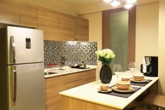 Θερμός τόνος του σχεδίου εσωτερικού πολυτέλειας της κουζίνας στη συγκυριαρχία, ως υπόβαθρο σχεδίου κουζινών Στοκ Εικόνες