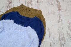 Θερμό πουλόβερ τρία σε ένα ελαφρύ ξύλινο υπόβαθρο, με το διάστημα για το κείμενο μοντέρνη έννοια Στοκ Εικόνες