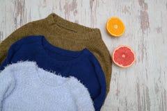 Θερμό πουλόβερ τρία σε ένα ξύλινο υπόβαθρο Πορτοκάλι και γκρέιπφρουτ Μοντέρνη έννοια, τοπ άποψη Στοκ Εικόνες