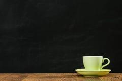 Θερμό πράσινο φλυτζάνι καφέ χρώματος στο ξύλινο πάτωμα Στοκ Εικόνα