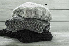 Θερμό πλεκτό πουλόβερ, τρία κομμάτια, ο Μαύρος, γκρι και λευκό σε ένα ξύλινο υπόβαθρο Στοκ Φωτογραφία