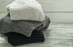 Θερμό πλεκτό πουλόβερ, τρία κομμάτια, ο Μαύρος, γκρι και λευκό σε ένα ξύλινο υπόβαθρο Στοκ φωτογραφία με δικαίωμα ελεύθερης χρήσης