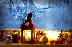 Θερμό φανάρι στο παγωμένο παράθυρο, χειμώνας μαγικός με τις ευπρέπειες Χριστουγέννων Στοκ Εικόνες
