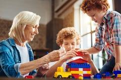 Θετικά απασχολημένα οικογενειακά μέλη που παίζουν με το σύνολο κατασκευής Στοκ εικόνα με δικαίωμα ελεύθερης χρήσης