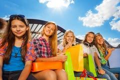 Θετικά κορίτσια με το ζωηρόχρωμο κάθισμα τσαντών αγορών Στοκ φωτογραφία με δικαίωμα ελεύθερης χρήσης