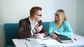 Θετικές αρσενικές και γυναίκες σπουδαστές που κάνουν την εργασία που ξοδεύει μαζί το χρόνο στην πανεπιστημιούπολη, συνάδελφοι που απόθεμα βίντεο
