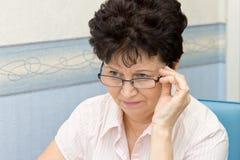 Θετική ανώτερη γυναίκα της Νίκαιας που φορά τα γυαλιά στο σπίτι Στοκ Φωτογραφίες