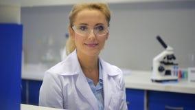 Θετική απασχολημένη γυναίκα που χαμογελά μετά από να ελέγξει τα έγγραφα στο εργαστήριο απόθεμα βίντεο
