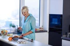 Θετική ευχαριστημένη συμπαθητική γυναίκα που κρατά ένα αιχμηρό μαχαίρι στοκ εικόνες
