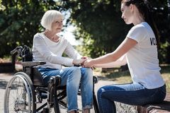 Θετική ηλικιωμένη γυναίκα που κρατά τα χέρια εθελοντών της Στοκ εικόνα με δικαίωμα ελεύθερης χρήσης