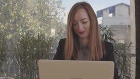 Θετική νέα γυναίκα με το προσωπικό Η/Υ απόθεμα βίντεο