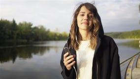 Θετική νέα γυναίκα που ακούει τη μουσική και που χορεύει κοντά σε έναν ποταμό απόθεμα βίντεο