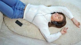 Θετική νέα γυναίκα που βρίσκεται στη χνουδωτή μουσική ακούσματος ταπήτων που χρησιμοποιεί το smartphone και τα ακουστικά απόθεμα βίντεο