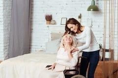 Θετική νέα γυναίκα που φροντίζει τη γιαγιά της στην αναπηρική καρέκλα Στοκ Εικόνες