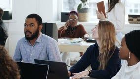 Θετική νέα ξανθή γυναίκα και όμορφη αφρικανική συνεδρίαση ανδρών στην επιτραπέζια συνεδρίαση γραφείων σύγχρονο ελαφρύ απόθεμα βίντεο