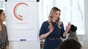 Θετική νέα χαμογελώντας επιχειρησιακή γυναίκα διευθυντών που παρουσιάζει το πρόγραμμα στους συνεργάτες στη σύγχρονη συνεδρίαση τω απόθεμα βίντεο