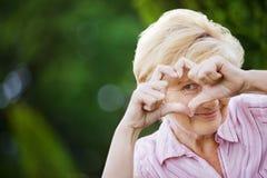 Θετική σκέψη. Ευτυχής αστεία ανώτερη γυναίκα που παρουσιάζει σύμβολο της καρδιάς Στοκ Εικόνες