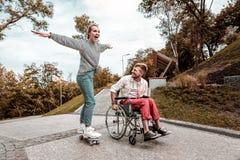 Θετική συνεδρίαση ατόμων στην αναπηρική καρέκλα και τη φίλη του που οδηγούν skateboard της στοκ φωτογραφία με δικαίωμα ελεύθερης χρήσης