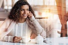 Θετική συνεδρίαση γυναικών χαμόγελου στον πίνακα και να εξετάσει το παράθυρο Στοκ εικόνα με δικαίωμα ελεύθερης χρήσης