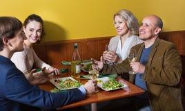 Θετικοί άνθρωποι μεσαίων τάξεων που απολαμβάνουν τα τρόφιμα και το κρασί Στοκ Φωτογραφίες