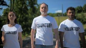 Θετικοί διεθνείς εθελοντές που πηγαίνουν να βοηθήσει τους ανθρώπους απόθεμα βίντεο
