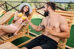 Θετικοί και ευχάριστοι άνθρωποι που κάθονται στα sunbeds και που εξετάζουν ο ένας τον άλλον Χαμογελούν Το ζεύγος αγγίζει το ένα τ στοκ φωτογραφία
