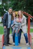 Θετικοί οικογενειακοί μητέρα και πατέρας με το παιχνίδι γιων και κορών στην παιδική χαρά Στοκ εικόνες με δικαίωμα ελεύθερης χρήσης