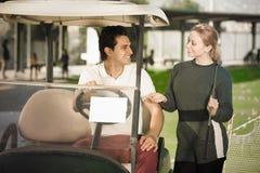 Θετικοί παίκτες γκολφ ανδρών και γυναικών που οδηγούν το κάρρο γκολφ Στοκ Φωτογραφίες