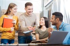 Θετικοί σπουδαστές που χαμογελούν χαρωπά μελετώντας από κοινού Στοκ εικόνα με δικαίωμα ελεύθερης χρήσης