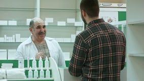 Θετικός ανώτερος druggist που δίνει την ιατρική πελατών στο φαρμακείο φιλμ μικρού μήκους