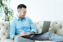 Θετικός απασχολημένος επιχειρηματίας που παίρνει τις σημειώσεις και το χαμόγελο Στοκ Φωτογραφίες